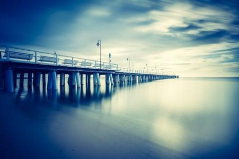 pier beach blue yellow water calm shutter speed slow