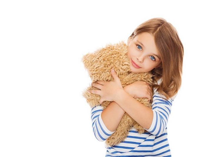 child cuddling teddy