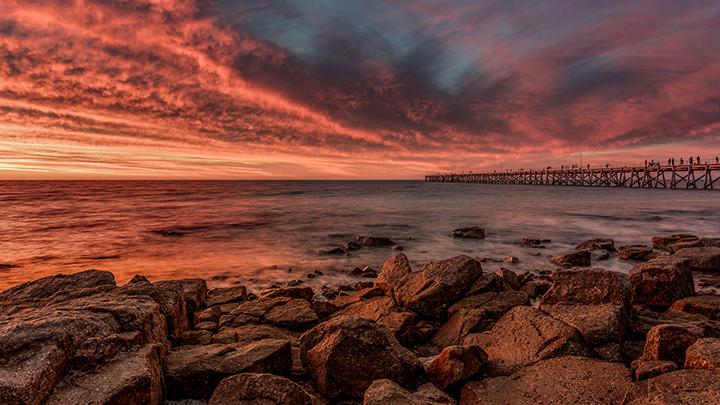 landscape water rocks pier sunset red pink