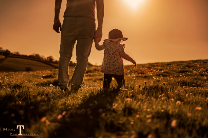 father daughter sunset red orange shadows evening walking hands holding love