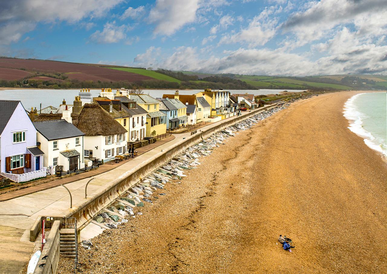 beach cove houses shore pebbles water sea sky landscape village