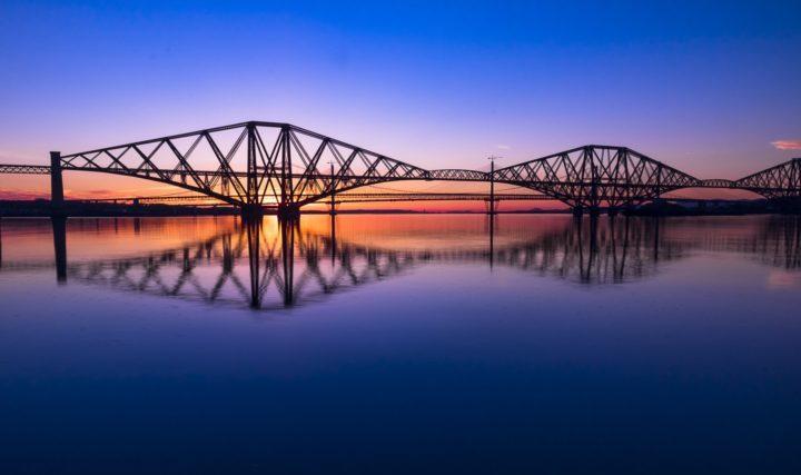 bridge night sun set colour blue red orange yellow reflection water calm river