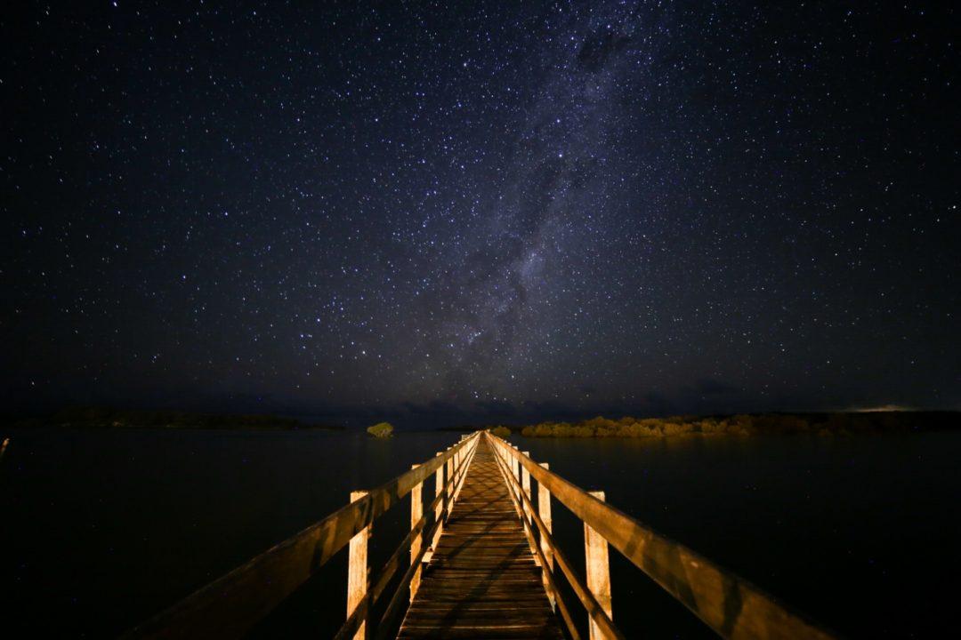 stars night pier leading lines milky way flash shadow