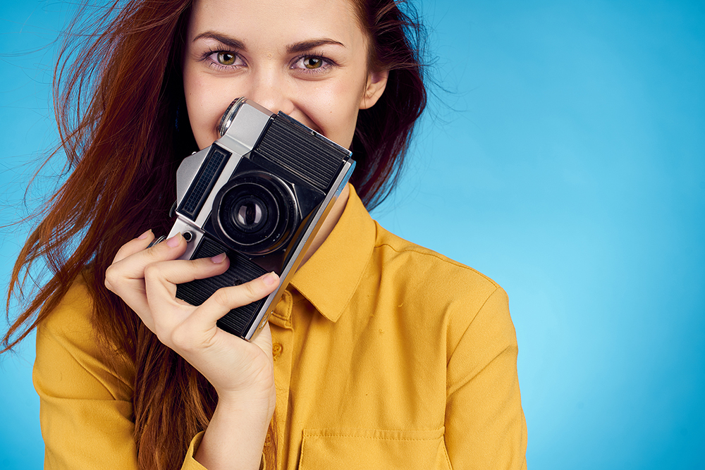 portrait photography female camera yellow top blue background smiling