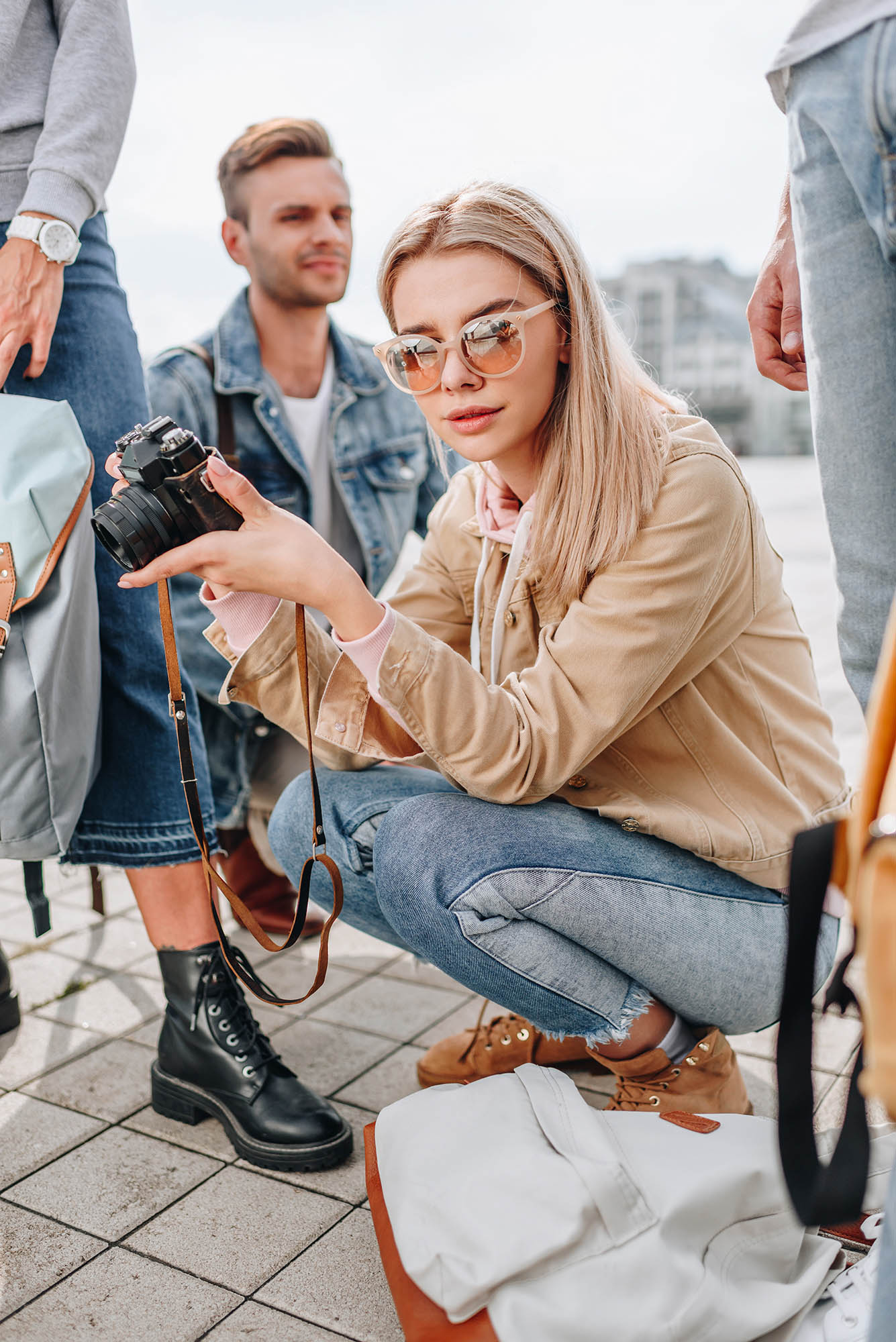 girl sunglasses crouched crowd camel jacket blonde hair blue jeans street photography portrait city people camera subject light how to tutorial guide