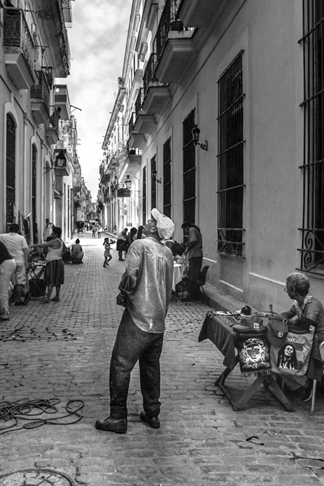man looking up at building in alleyway of small town street photography portrait city people camera subject light how to tutorial guide
