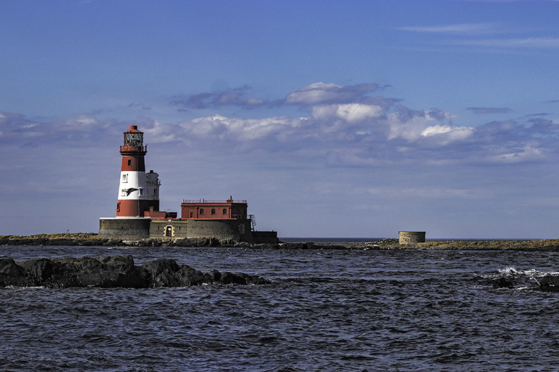 lighthouse red white tower water rocky outcrops Fred West
